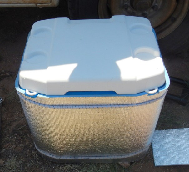 Here's the cooler wrapped with the foam backpackers pad. I just used bungee cords wrapped around it at the top and bottom to hold it in pace. I cut two pieces out for it to sit on and I glued one piece to the top.