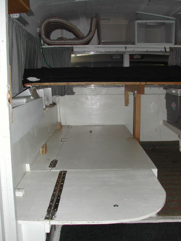 Notice the fold-down extension to the five foot couch to turn it into a 6 foot bed. Across the truck bed is the removable upper bunk with supports in place.