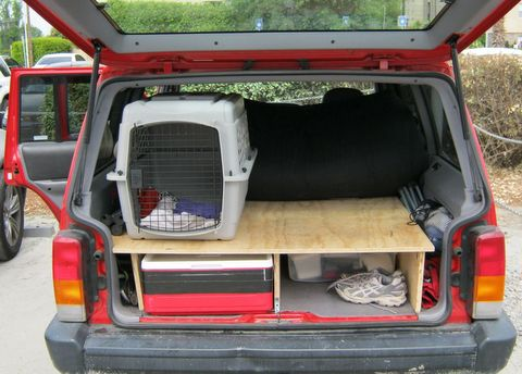 "A view of the back of the Cherokee in ""day position."" Sprocket quickly refused to ride in his crate preferring the freedom of the whole back of the rig. Our bedding folded under the mattress vaguely protecting it from puppy hair. When he was wet or sandy he went into his crate. You can also see our stackable cooler that we cut the handles off to fit into the available space."