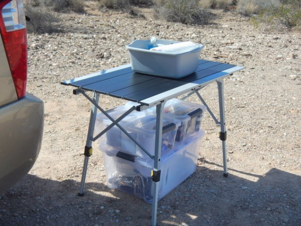 The one thing he couldn't fit inside the Sedona was a counter-top so he got this folding table and sits it outside the back hatch. He does dishes inside the tub and most of his cooking essentials fits in the two plastic totes. Perfect!