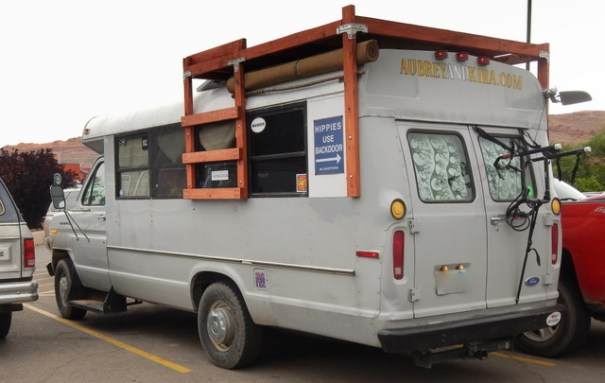 My guess is that at one time this was a sxhool bus, but now it is adventure-central for some free-spirits who ramble around the country living life to it's fullest. Apparently they couldn't afford a roof rack, so they just built their own out of wood.