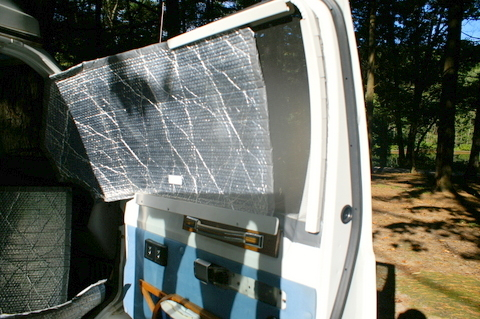 This view of the front passenger door shows how he mounts the Reflectix. He screwed in channels above, below and on one end of the window and just slides the Reflectix into the channel when he wants to use it, and it is easily removed when traveling.