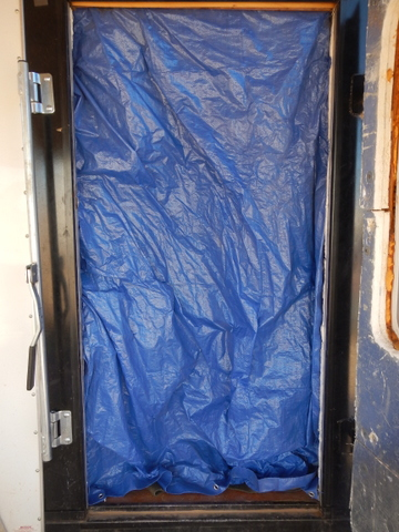 The door into my trailer doesn't seal well, so I hang this tarp on the inside of it to stop drafts...