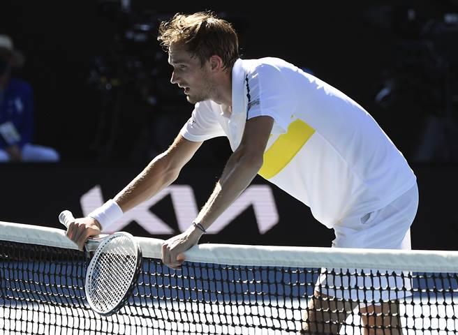 麥維德夫經歷一場苦戰,累得撐著球網稍微喘息。(美聯社)