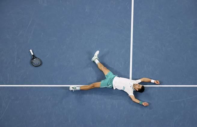 喬柯維奇躺在地上慶祝自己再度稱霸澳網男單。(美聯社)
