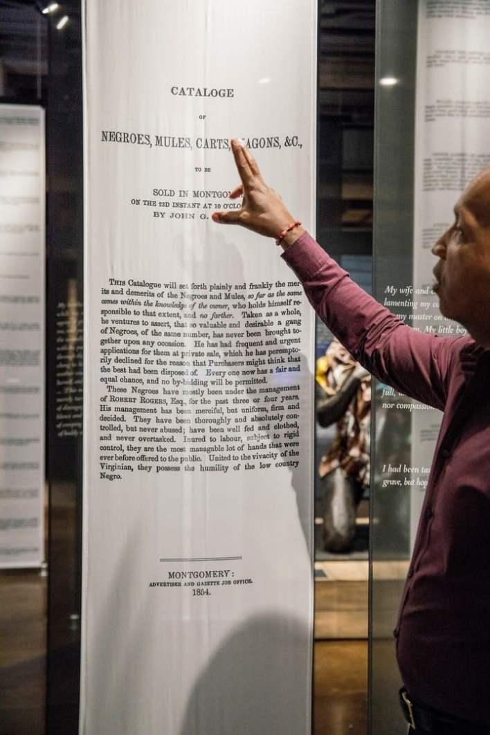 Bryan Stevenson, fundador de la Inciativa de Justicia Igualitaria, lee la introducción de un catalogo de 1854 sobre esclavo. / Audra Melton/The New York Times