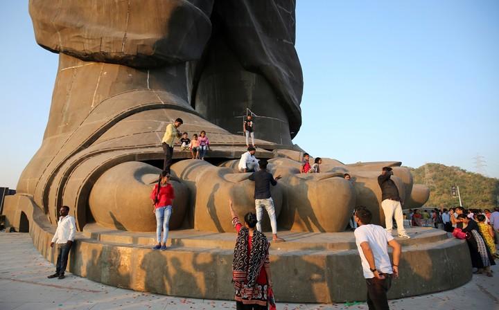 Como liliputenses, los visitantes trepan a los pies del gigante de bronce. REUTERS/AMIT DAVE