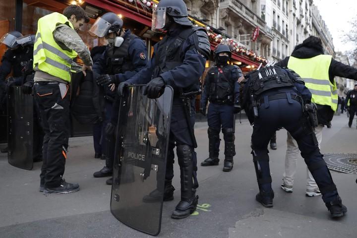 Policías revisan a un manifestante que se acerca al Arco del Triunfo. (AFP)