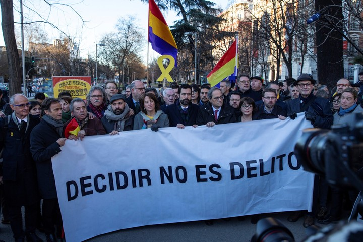 """El presidente de la Generalitat, Quim Torra (4 der), y el presidente del Parlament, Roger Torrent (5 izq), tras una pancarta con el lema """"Decidir no es delito"""", a su llegada al Tribunal Supremo (EFE)."""