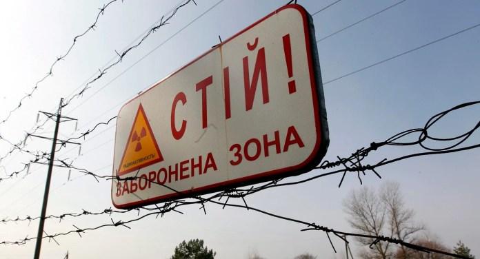 """Una placa con la leyenda """"Stop. Zona Prohibida"""" y situada sobre la alambrada que rodea la zona de exclusión de 30 kilómetros alrededor de la central nuclear de Chernobyl , cerca del puesto de control de Dytyatky, en Ucrania.   EFE/Sergey Dolzhenko"""