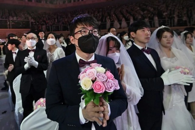 A couple wearing protective face masks attend a mass wedding ceremony organised by the Unification Church at Cheongshim Peace World Center in Gapyeong on February 7, 2020. - South Korea has confirmed 24 cases of the SARS-like virus so far and placed nearly 260 people in quarantine for detailed checks amid growing public alarm. (Photo by Jung Yeon-je / AFP)