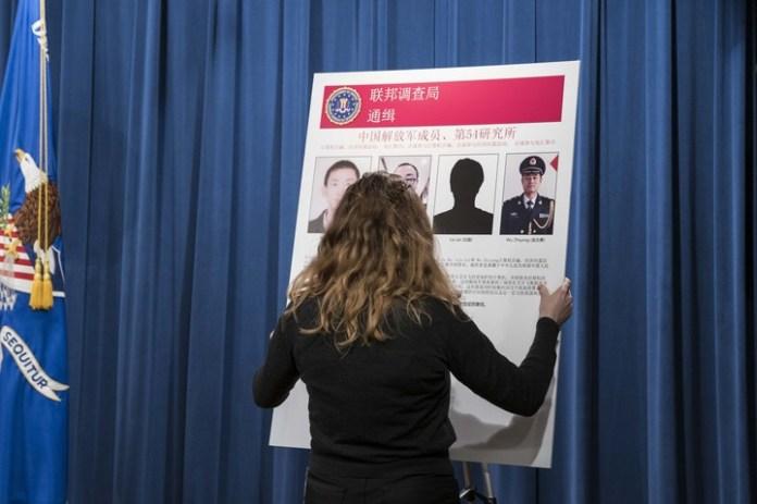 Acusados. Una funcionaria del Departamento de Justicia exhibe un cuadro con los datos de los cuatro militares chinos imputados por EE.UU. de hackeo en 2017 (AFP).