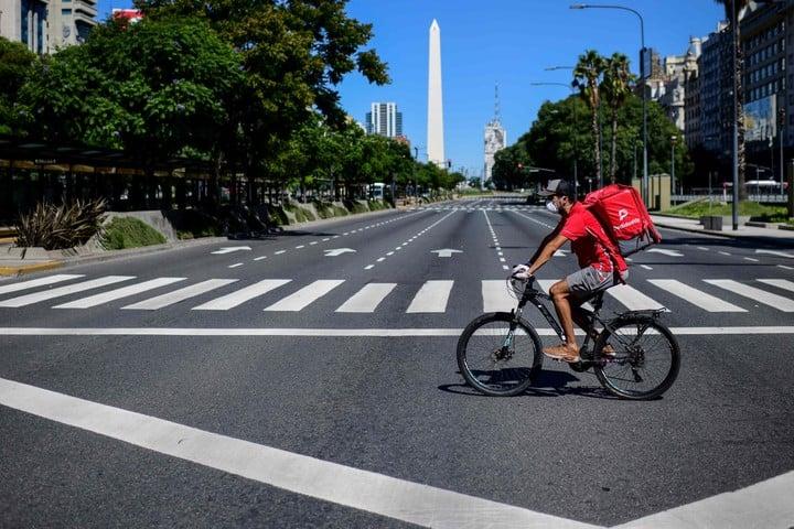 Un repartidor en una bicicleta a lo largo de la Avenida 9 de Julio..(Foto de Ronaldo SCHEMIDT / AFP)
