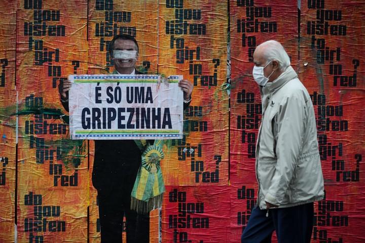 """Una imagen del presidente brasileño Jair Bolsonaro sosteniendo un cartel con su polémico comentario sobre la COVID-19 al inicio de la pandemia, """"Es solo una gripecita"""". Foto: EFE"""