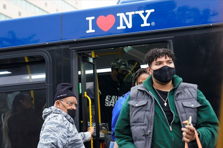 Passengers wearing a chinstrap get off a bus in New York at the end of 2020. Photo.  AP