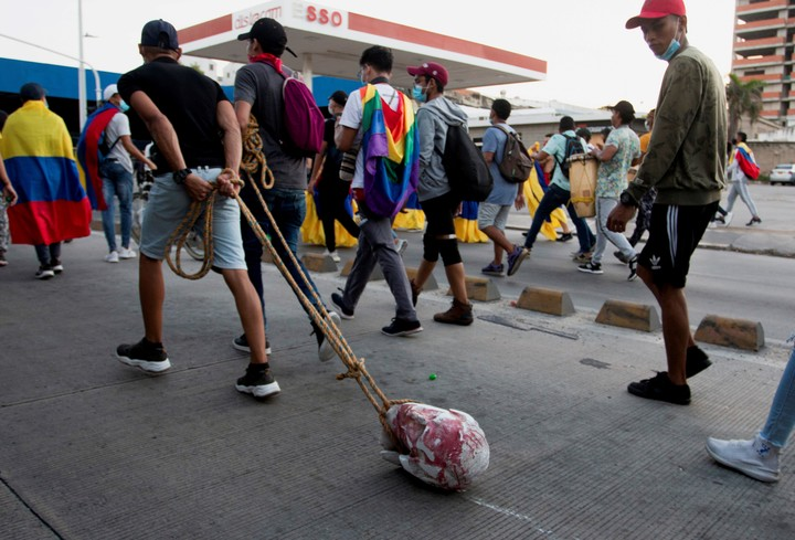 Protesters drag the head of the statue of Columbus, after toppling it during the protests, in Barranquilla.  Photo: AFP