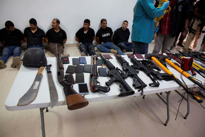 The suspects in the murder, with the weapons seized by the Haitian police as part of the investigations.  Photo: AP