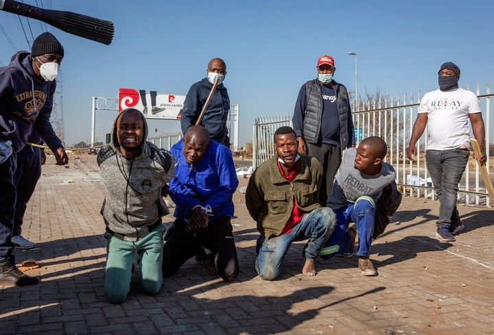 Men detained by civilians after looting in Johannesburg.  AP Photo