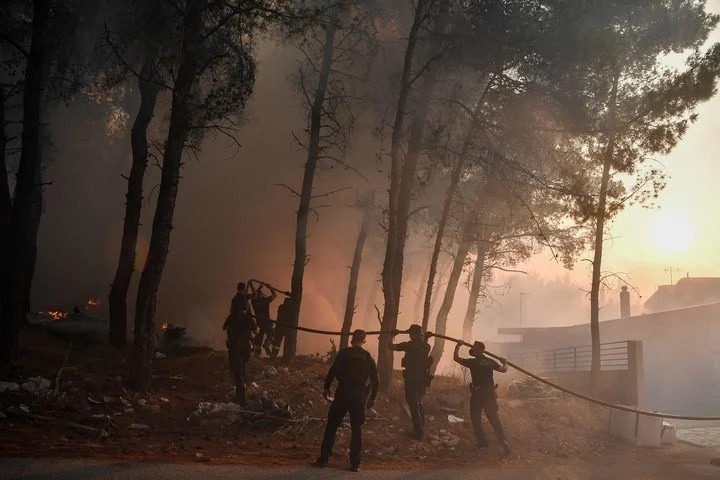 TOPSHOT - Police officers help firefighters to extinguish a fire in Thrakomakedones, near Mount Parnitha, north of Athens, on August 7, 2021. - Hundreds of firefighters battled a blaze on the outskirts of Athens as several fires raged in Greece.  (Photo by Louisa GOULIAMAKI / AFP)