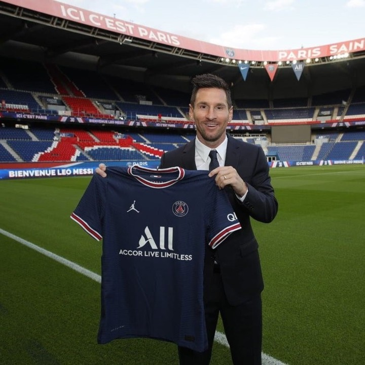 Lionel Messi poses with the shirt of PSG, his new club