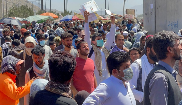 A photo prior to the attacks shows Afghans showing their permits to leave the country, outside the airport.  Photo: Reuters