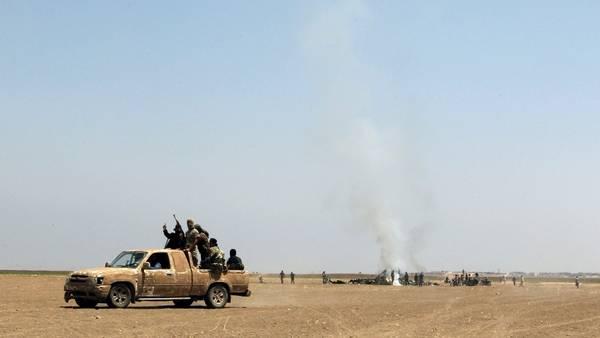 Rebeldes sirios del grupo Fatah al Sham junto a los restos del helicóptero ruso derribado en la provincia de Idlib. REUTERS
