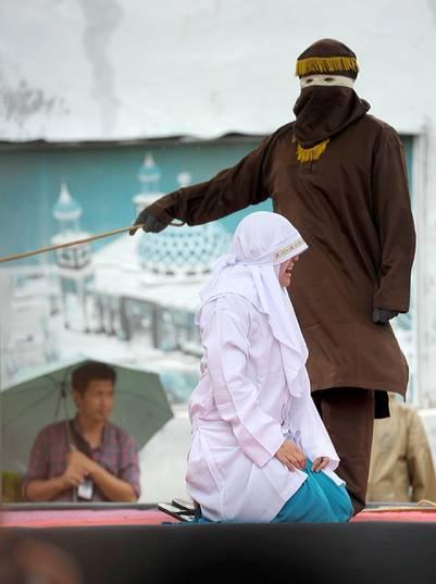 Una mujer es castigada en público por violar la estricta ley islámica en Banda Aceh, Indonesia. / AFP