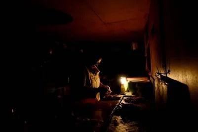 Una mujer cocina con luz de velas en un puesto de comida en la calle, durante un corte de energía en Tinaquillo en el estado de Cojedes, Venezuela. (REUTERS)