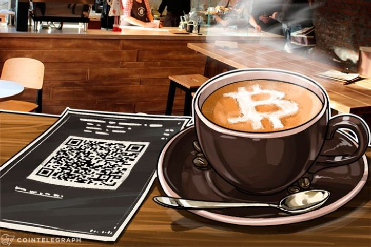 A cup of coffee and a paper wallet for paying with Bitcoin