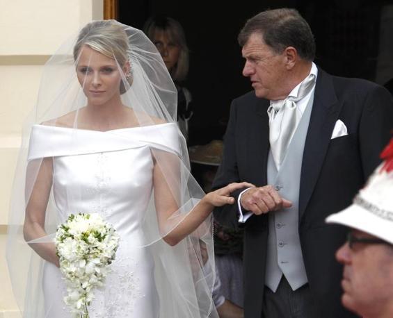 Charlene, al braccio del padre Michael, indossa  un abito nuziale firmato da Giorgio Armani (Reuters)