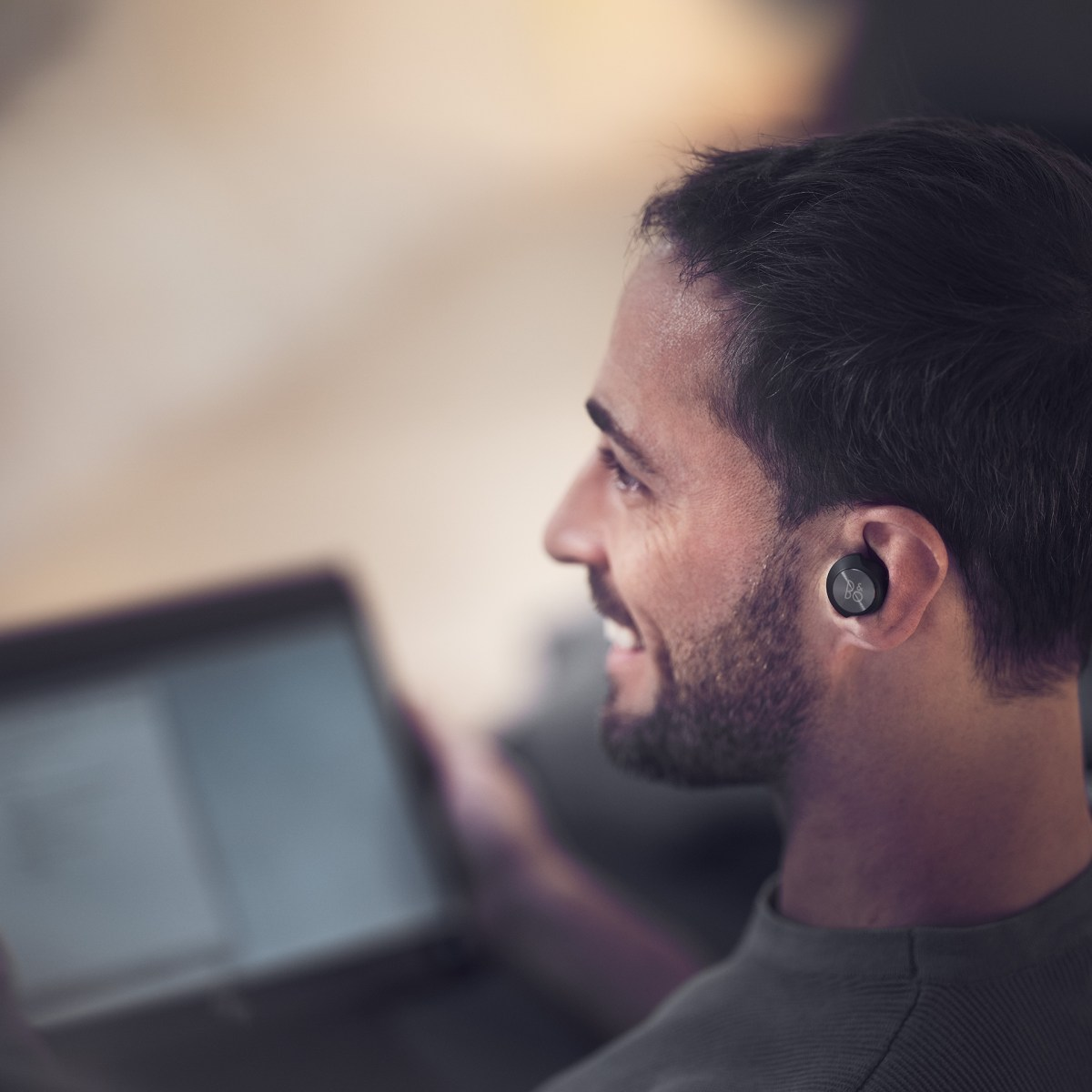 A man wearing Beoplay EQ while working from home