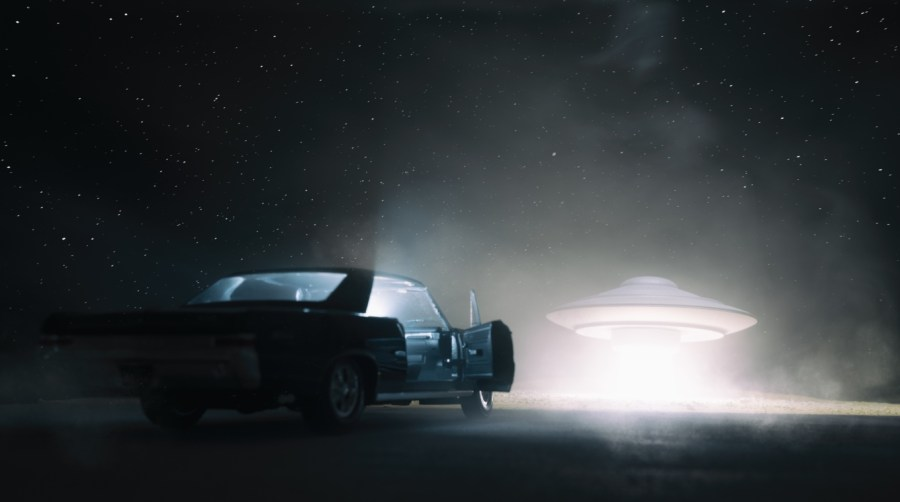 Bright UFO hovers infront of a car