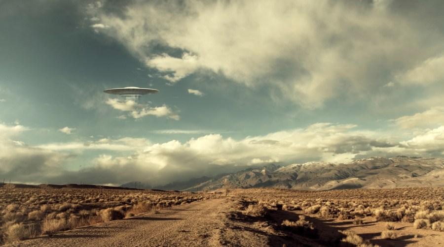 UFO flying over a desert road