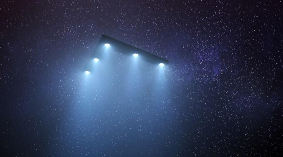 Triangular UFO flies against a starry sky