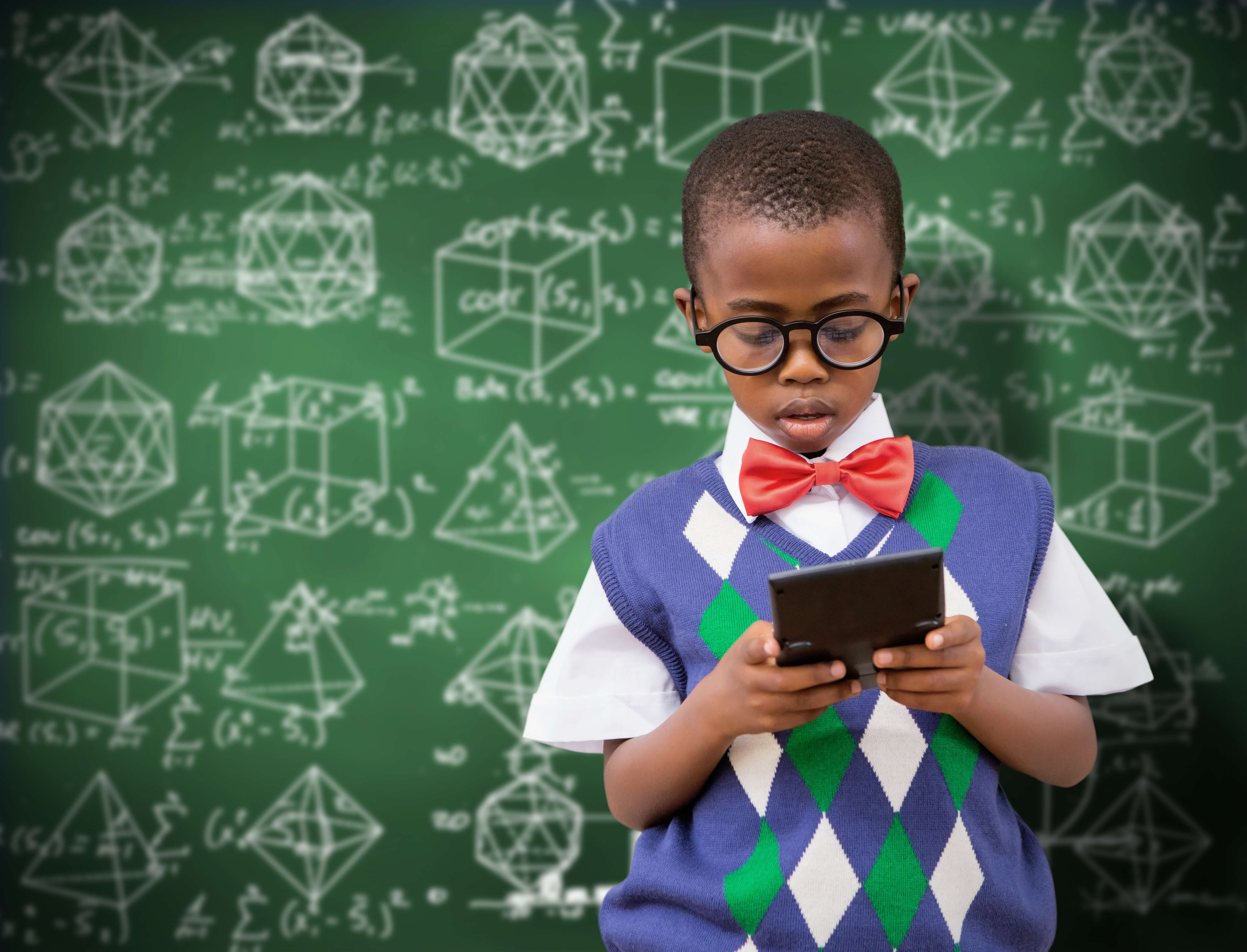 Un niño sosteniendo una calculadora frente a una pizarra.