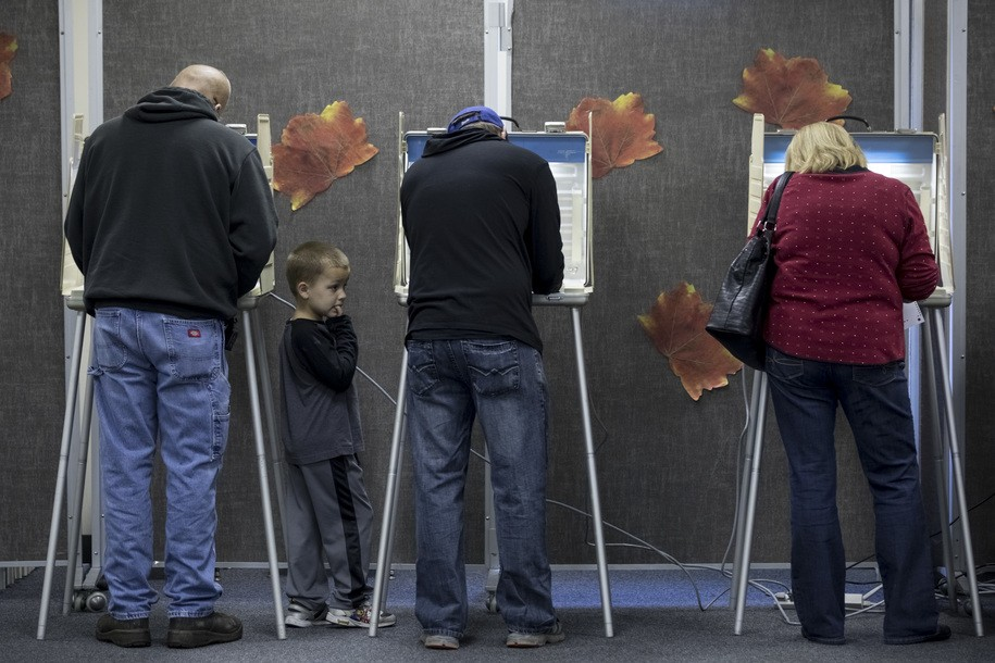 LEVASY, MO - NOVEMBER 08: Voters along with a child cast their ballots on November 8, 2016 in Levasy, Missouri, United States. Americans across the nation are picking their choice for the next president of the United States. (Photo by Whitney Curtis/Getty Images)