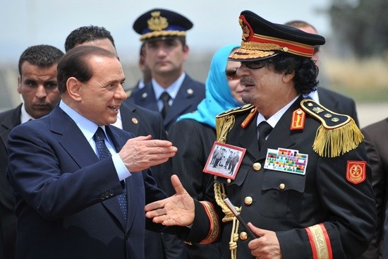Libya's leader Moamer Kadhafi (R) is greeted by Italian Prime Minister Silvio Berlusconi upon his arrival for his first visit to Italy on June 10, 2009 at Ciampino airport. The three-day visit seals a major rapprochement since Italy signed a deal with its former 1911 to 1947 colony last year pledging five billion dollars (3,5 billion euros) over the next 25 years as compensation for colonising it. Rome has also stepped up its relations with Tripoli in recent years in a bid to rein in a massive influx of clandestine migrants, many of whom come by boat from Libya across the Mediterranean.  AFP PHOTO / CHRISTOPHE SIMON (Photo credit should read CHRISTOPHE SIMON/AFP/Getty Images)