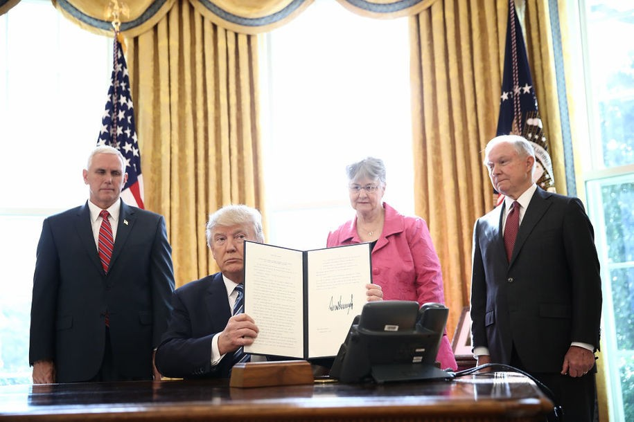 WASHINGTON, DC - FEBRUARY 09:  U.S. President Donald Trump shows an executive order he signed in the Oval Office of the White House February 9, 2017 in Washington, DC. Prior to signing the three executive orders, Trump participated in the swearing in ceremony for new Attorney General Jeff Sessions (R) along with U.S. Vice President Mike Pence (L) and Sessions's wife Mary (2nd R).  (Photo by Win McNamee/Getty Images)