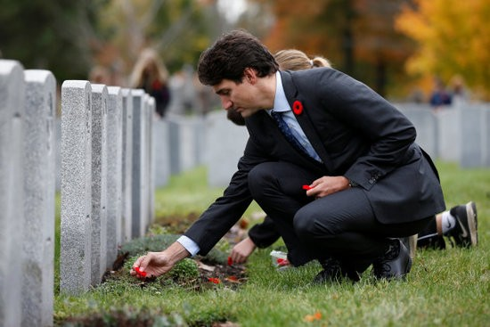 Canada's Prime Minister Justin Trudeau places a poppy at a grave during an event to mark the upcoming Veterans' Week and 100th anniversary of the Battle of Passchendaele at the National Military Cemetery in Ottawa, Ontario, Canada, November 3, 2017. REUTERS/Chris Wattie