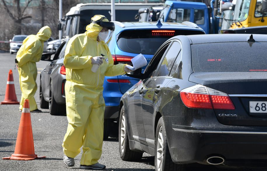 "Medical members wearing protective gear guide drivers with suspected symptoms of the COVID-19 coronavirus, at a ""drive-through"" virus test facility in Goyang, north of Seoul, on February 29, 2020. - South Korea reported on February 29 its biggest surge in new coronavirus cases and concerns grew of a possible epidemic in the United States as the World Health Organization raised its risk alert to its highest level. (Photo by Jung Yeon-je / AFP) (Photo by JUNG YEON-JE/AFP via Getty Images)"