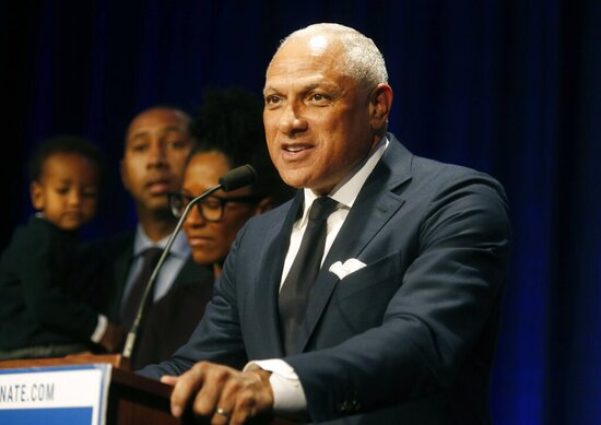FILE - In this Nov. 27, 2018 file photo, Mississippi Democrat Mike Espy stands with family members as he talks to supporters in a crowded auditorium at the Mississippi Civil Rights Museum in Jackson, Miss., after losing the runoff election. On Tuesday, Nov. 12, 2019, Espy announced another run for U.S. Senate, setting up a 2020 rematch with Republican Cindy Hyde-Smith.  (AP Photo/Charles A. Smith, File)
