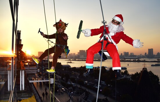 Workers in Santa Claus (R) and reindeer (L) costumes clean windows outside a shopping mall along Tokyo's waterfront on December 24, 2014. The costumes were worn as part of a Christmas promotional event to attract shoppers.   AFP PHOTO / Yoshikazu TSUNO        (Photo credit should read YOSHIKAZU TSUNO/AFP via Getty Images)