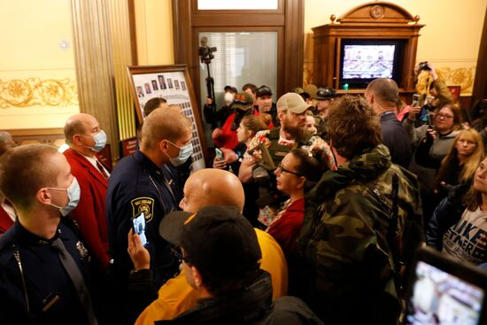 Protestors try to enter the Michigan House of Representative chamber and are being kept out by the Michigan State Police after the American Patriot Rally organized by Michigan United for Liberty protest for the reopening of businesses on the steps of the Michigan State Capitol in Lansing, Michigan on April 30, 2020. - The group is upset with Michigan Gov. Gretchen Whitmer's mandatory closure to curtail Covid-19. (Photo by JEFF KOWALSKY / AFP) (Photo by JEFF KOWALSKY/AFP via Getty Images)
