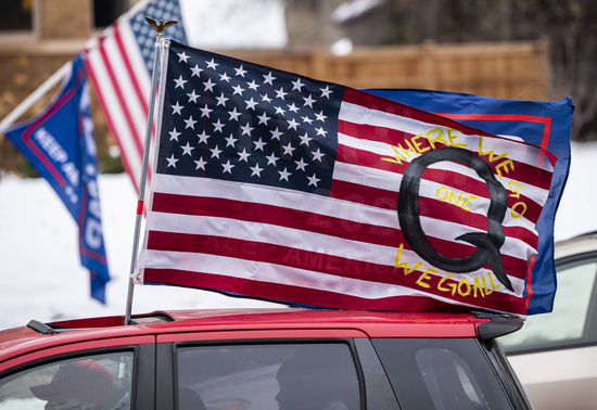 ST PAUL, MN - NOVEMBER 14: A car with a flag endorsing the QAnon drives by as supporters of President Donald Trump gather for a rally outside the Governor's Mansion on November 14, 2020 in St Paul, Minnesota. Thousands have gathered in cities around the country today to contest the results of the election earlier this month. (Photo by Stephen Maturen/Getty Images)
