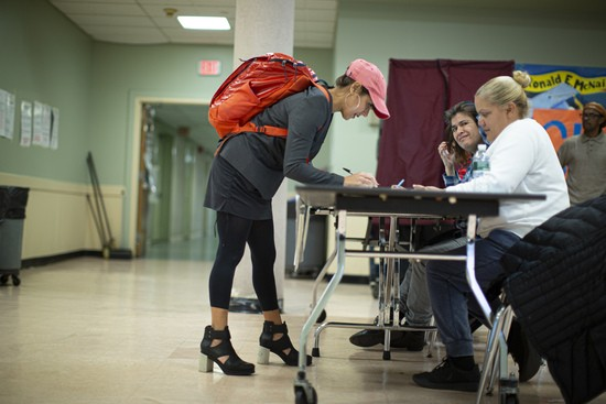 JERSEY CITY, NJ - November 05: A woman fills out documents before casting her ballot at a polling station in Jersey City, New Jersey, November 5, 2019.  Voters will decide on ballot measurements to regulate the short-term rental industry, and if passed, the new rules will include a 60-day annual cap cap, and existing hosts will have to obtain city permits.  (Photo by Kina Betancourt / Getty Images)