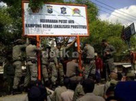 Satpol PP memasang plakat 'Kelurahan Putat Jaya Kampung Bebas Lokalisasi Prostitusi'.