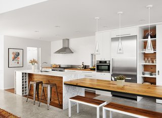 Kitchen, Pendant Lighting, Marble Counter, Wood Cabinet, White Cabinet, Wall Oven, Range Hood, Refrigerator, Concrete Floor, Open Cabinet, Undermount Sink, Recessed Lighting, Range, and Subway Tile Backsplashe Architect Kevin Alter integrated wood from the original bungalow into the kitchen and covered the island in Carrara marble, with an interior clad in wood. A long table extends from the side of the island, and wine storage is integrated into one end of the island. New appliances include a Wolf range, a Broan hood, and a Miele oven and refrigerator. The Fucsia pendant lights are by Achille Castiglioni for Flos.