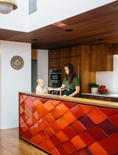 Kitchen, Wood Cabinet, Medium Hardwood Floor, Wall Oven, Ceiling Lighting, Recessed Lighting, and Pendant Lighting Aaron and Yuka Ruell transformed a 1950s Portland ranch house into a retro-inspired family home with plenty of spaces for their four children to roam. In the kitchen, interior designer Emily Knudsen Leland replaced purple laminate cabinets with flat-sawn eastern walnut, and added PentalQuartz countertops in polished Super White for contrast. The kitchen island is clad with original red tiles, and hanging cabinets above it were removed to maximize light and family-room views.