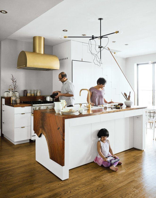 These 30 White Kitchens Are Anything But Ordinary - Photo 12 of 30 - A couple takes a minimalist approach to their Brooklyn apartment, focusing on supple materials, subtle gradations of color, and custom finishes by local craftsmen. The Mandayam–Vohra family gathers under one of Workstead's signature three-arm chandeliers, shown here in its horizontal configuration. Bartenschlager designed the white cabinets and is responsible for the walnut counters both on the kitchen island and near the stove.