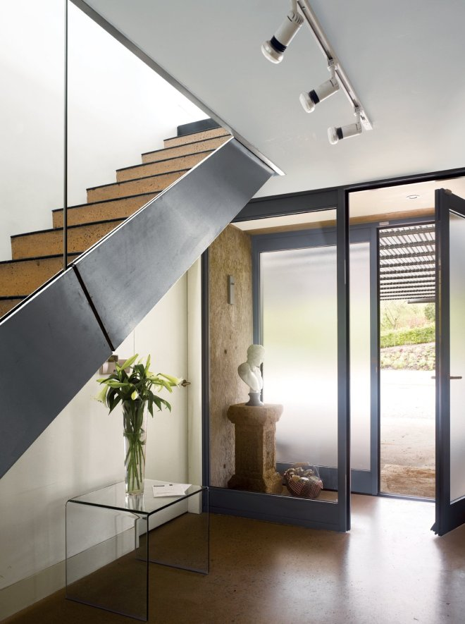 10 Smart and Surprising Under-Stair Design Solutions - Photo 8 of 10 - In homes that aren't short on square footage, the space under a staircase can be the perfect spot to create a beautiful ensemble of items like a grouping of your favorite vases or a special piece of furniture. In this home near Bristol, England, that was designed by Paul Archer, the space under a stairway was made visually, if not programmatically, useful by locating a glass table and vase with simple lines to create a subtle, minimalist vignette.